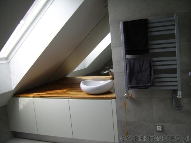 Łazienka pod niewielkim skosem, z oknami, które dodatkowo oświetlają małą powierzchnię. ...