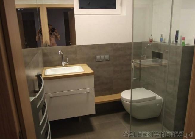 Projekt niewielkiej łazienki z wanną narożną. W łazience znajduje sięzlew podblatowy ...