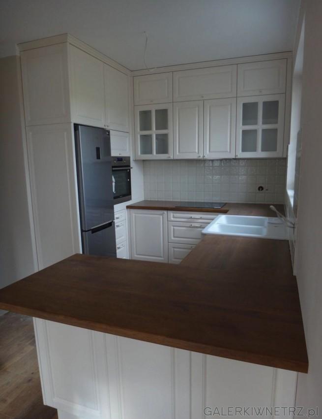 Urokliwa kuchnia w bieli i z drewnem. Kuchnia jest stylizowana na retro. Szafki ...