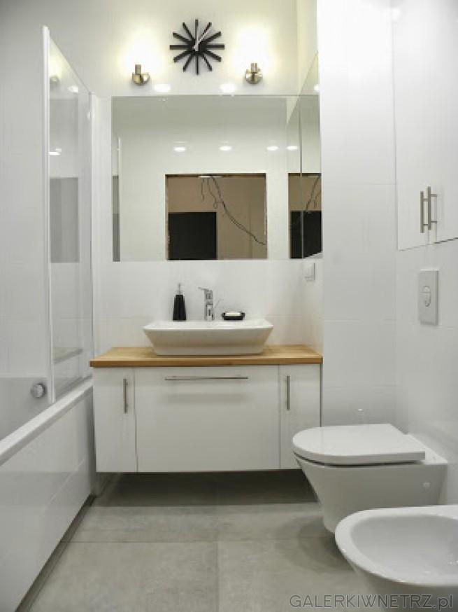 Ładnie zaaranżowana łazienka w bieli. W centralnym miejscu znajduje sięumywalka ...