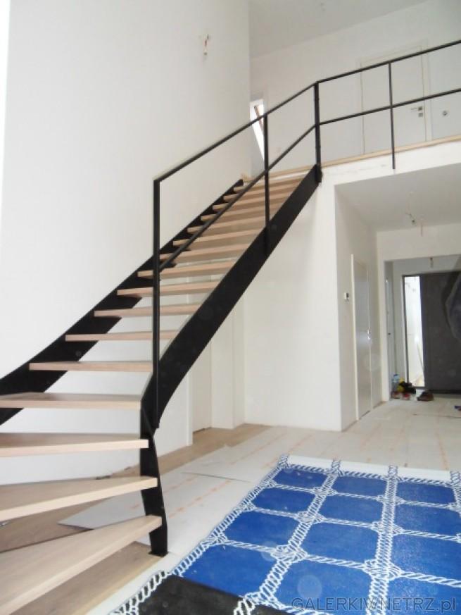 Minimalistyczne schody ażurowe z prostą czarną barierką - jest to poręcz idąca równolegle ...