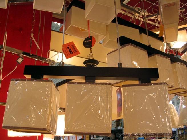 Żyrandol zbliżony do stylistyki mebli Essensi. Drewniana poprzeczka i trzy lampy ...