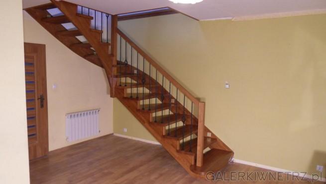 Klasyczne drewniane schody ażurowe. Wykonane z ciemnego drewna, wyglądają solidnie ...