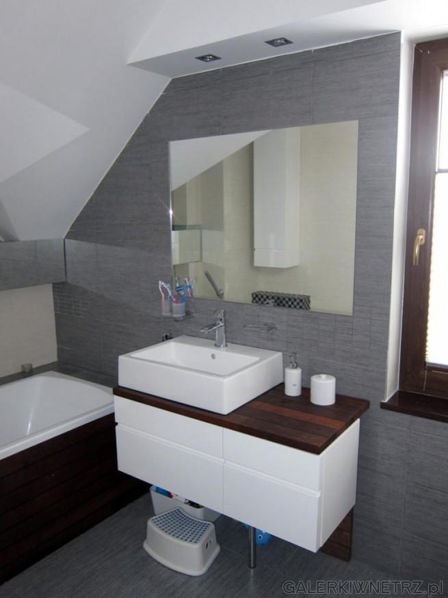 Aranżacja łazienki z wieloma skosami. W tej łazience dominująprzede wszystkim szarości, ...