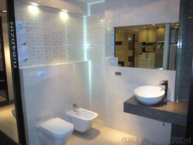 Jasna, świetlista łazienka utrzymana w kolorze bieli nieco przełamanej beżem. W ...