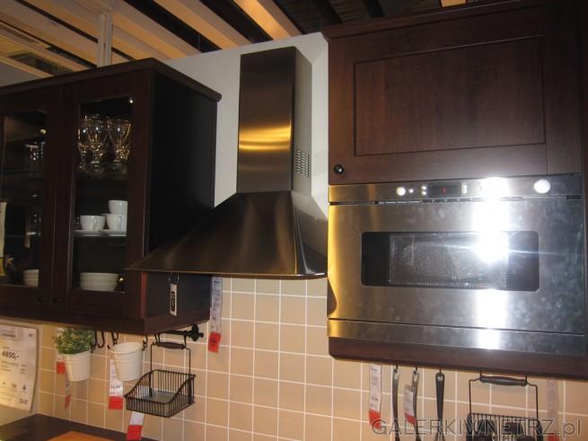 Oprócz ciemnobrązowych mebli widzimy srebrne urządzenia: srebrny okap kuchenny przymocowywany ...