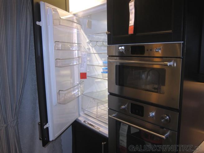 Zabudowana lodówka w aranżacji IKEI, natomiast tuż obok znajdziemy srebrny piekarnik ...