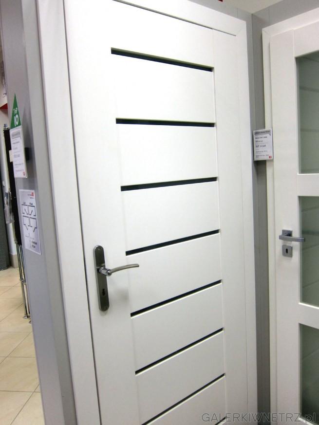 Białe drzwi wewnętrzne, bezprzylgowe, o prostym, minimalistycznym wyglądzie, z wąskimi, ...