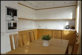 Biała kuchnia z dużym drewnianym stołem i drewnianymi szafkami