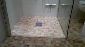 Mała łazienka z dużą kabiną z drewnem na ścianie i mozaikąna podłodze