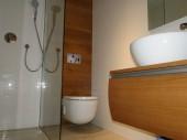 Łazienka z prysznicem walk-in oraz białą mozaikąTubądzin i drewnem