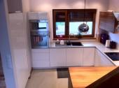 Kwadratowa kuchnia z oknem i słupkiem z mikrofalą i piekarnikiem oraz małym barem do jedzenia śniadania