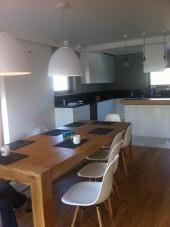 Jadalnia z dużym stołem z kuchnią w bieli
