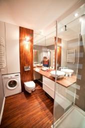 Ładna łazienka z drewnianą podłogą i umywalką nablatową