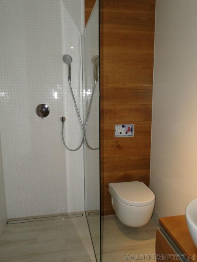 Aranżacja łazienki gdzie dominują biel i naturalne drewno. Pod prysznicem biała ...