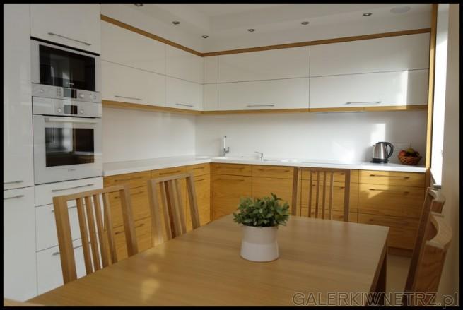 Aranżacja bardzo eleganckiej kuchni urządzonej w bieli z dodatkiem jasnego drewna. ...