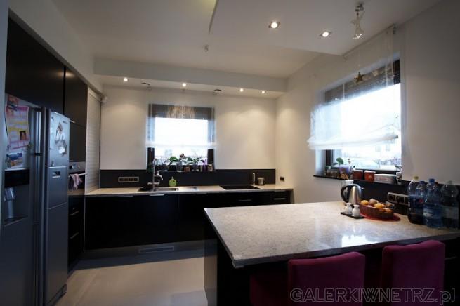 Duża, biało-czarna kuchnia. Okna z delikatnymi zasłonami powiększają optycznie ...