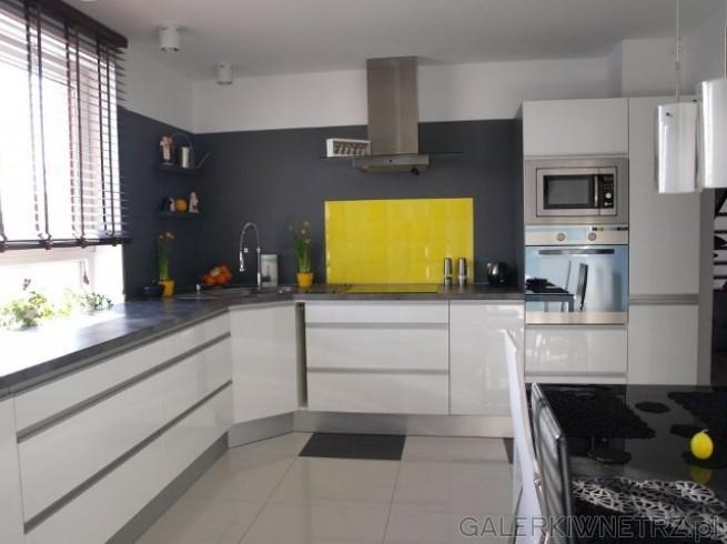 Duża kuchnia w kolorze grafitowo-białym, przełamana żółtymi, soczystymi dodatkami. ...
