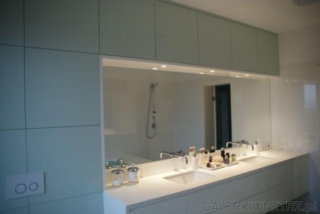Elegancka, prosta łazienka w całkowitej bieli. Na ścianie znajdują siępłytki Procelanosa ...