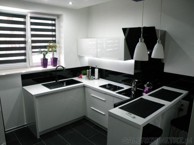 Biało-czarna kuchnia z niewielką ilością fioletu. Podłogi są czarne, złożone ...