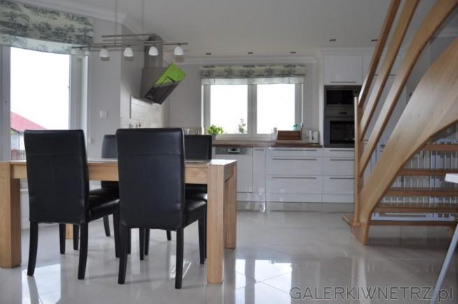 Duże schody oraz stół w kolorystyce zbliżonej do koloru blatów. Czarne krzesła ...