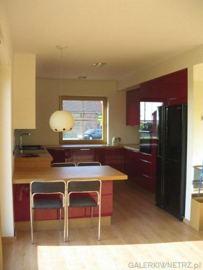 Kuchnia otwarta na pokój, jasne ściany oświetlają małe pomieszczenie