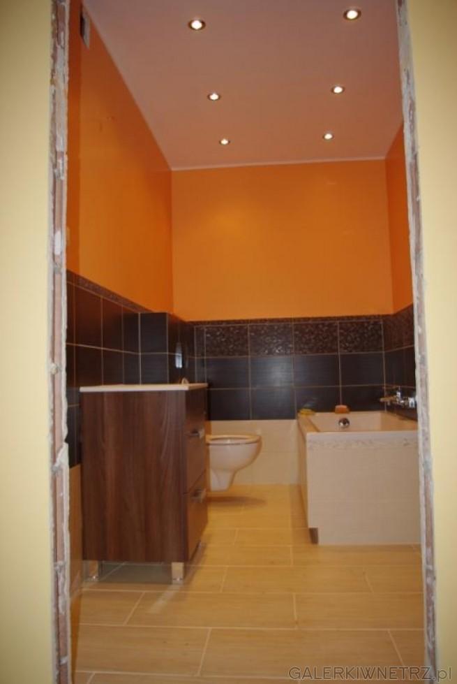 Aranżacja małej łazienki w intensywnym kolorze pomarańczowym. Drewniana półka z ...