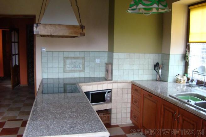Ciepła rodzinna kuchnia z beżami, brązami i zieleniami. Część ścian jest beżowa, ...