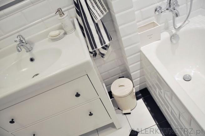 Łazienka utrzymana w bieli z niewielką ilościączerni na podłodze i w dodatkach. ...