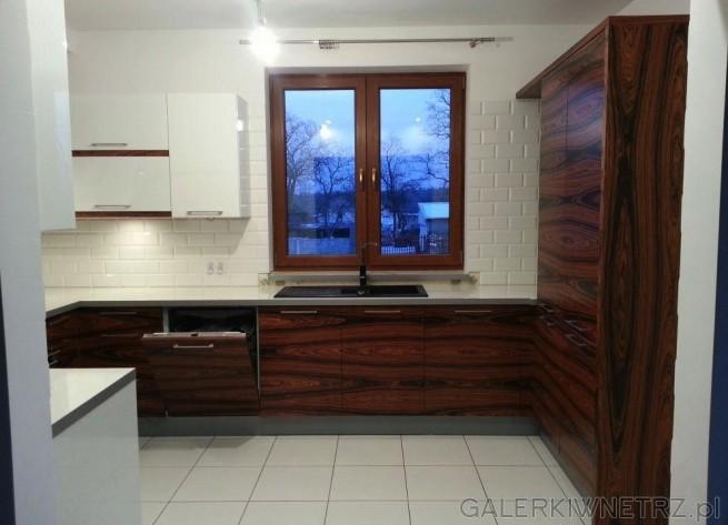 Elegancka, prosta kuchnia gdzie dominuje drewno palisandrowe i biel. Ściany są białe ...