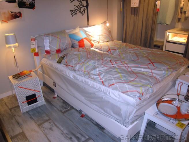 Aranżacja sypialni z dwuosobowym, białym łóżkiem. W sypialni znajduje siętakże ...