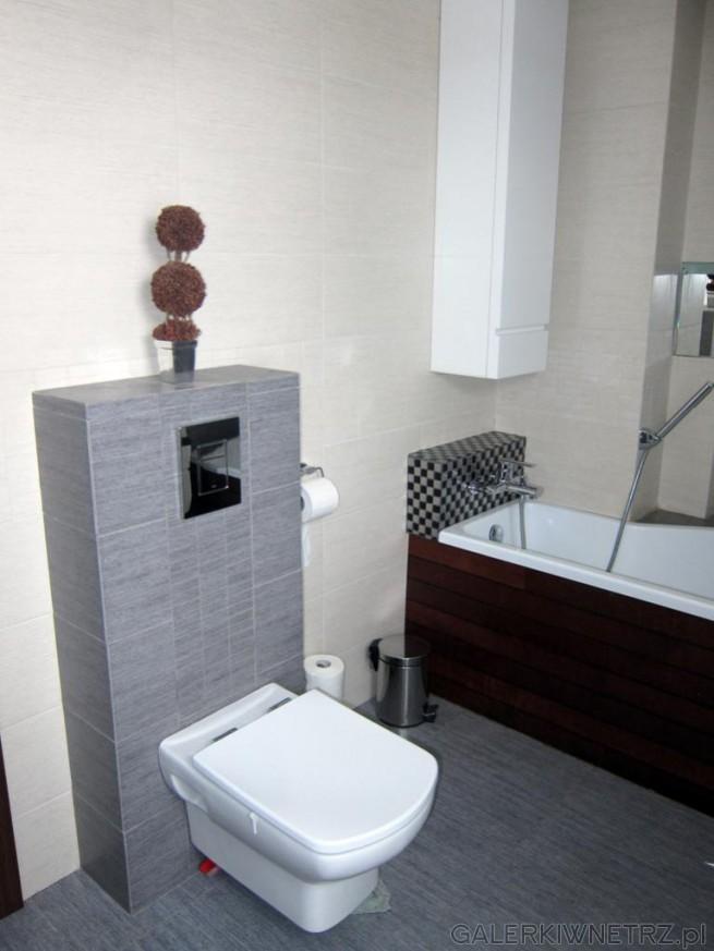 Łazienka w szarościach i beżach. Miska WC podwieszana na wysuniętej kolumience obudowanej ...
