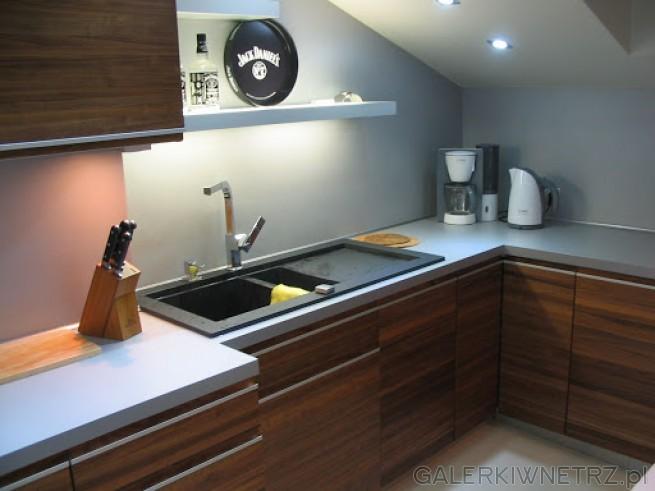 Kuchnia na poddaszu, sufit pod lekkim skosem. Blaty w kolorze aluminium. Na ścianach ...