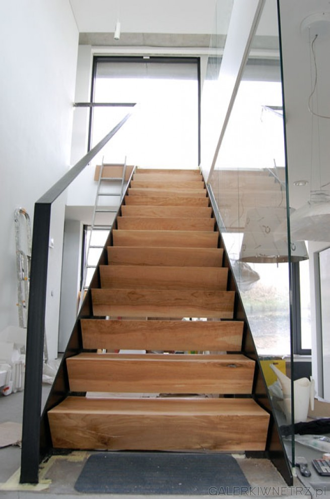 Schody ażurowe o wysokich stopniach. Wykonane z jasnego drewna, dzięki czemu nie ...