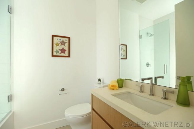 Urokliwa, niewielka łazienka pomalowana na biało. W łazience znajduje się biała ...