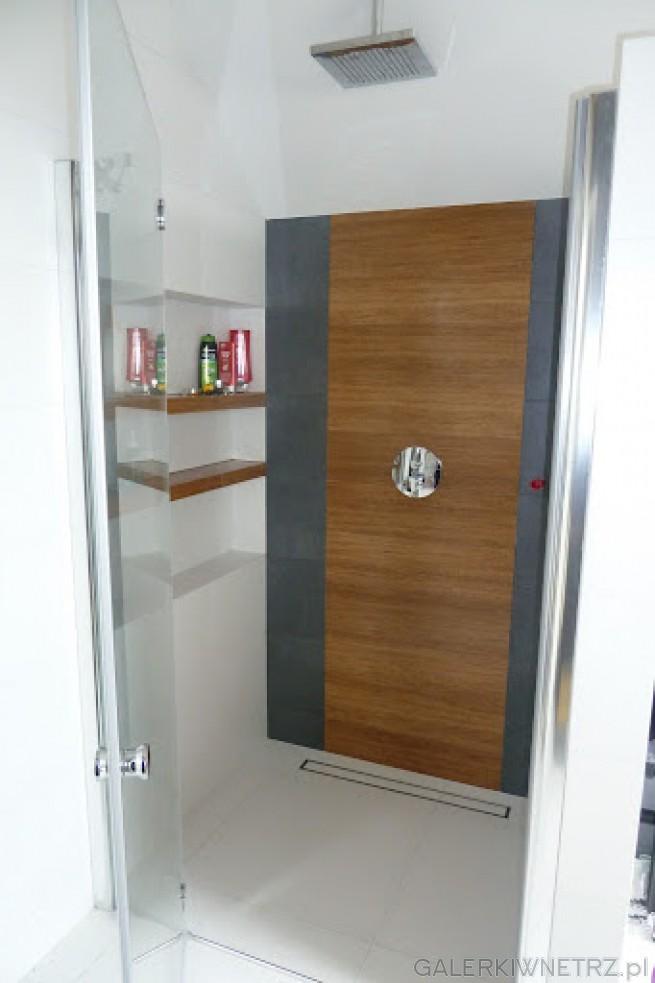 Prysznic zamontowany we wnęce, ze szklanymi otwieranymi drzwiami tworzy bardzo ...