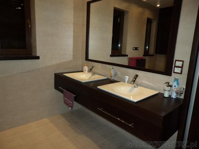 Duże lustro z ciemnobrązową framugą. Kwadratowe umywalki. Baterie przy umywalkach ...