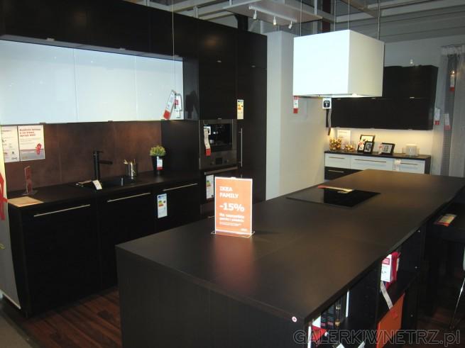 Aranżacja kuchni w ciemnej kolorystyce. Większość szafek i blat stołu zostały ...