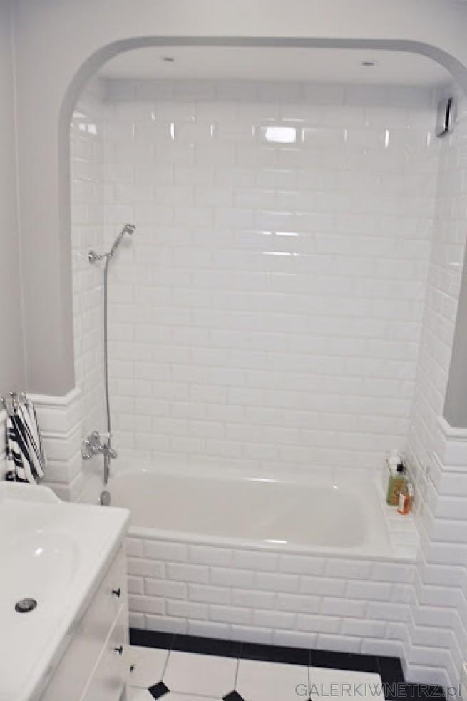 Biała wanna w tej aranżacji zajmuje całą szerokość łazienki, obudowana jest prostymi ...