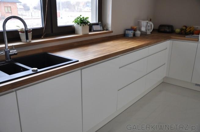 Blat Dębowy w białej kuchni ociepla duże, przestrzenne wnętrze. Na podłodze Gres ...