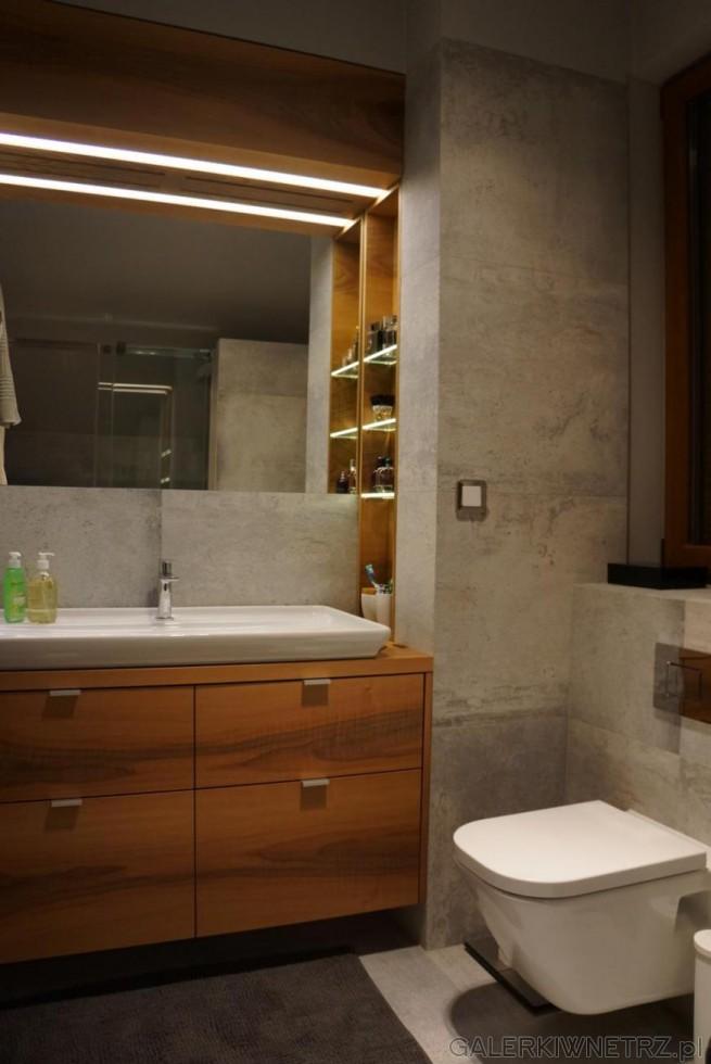 Piękna łazienka z dominacją szarości i drewna. Na ścianach znajduje sięszary gres ...