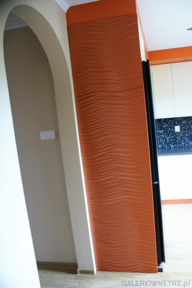 Miedziana zabudowa lodówki i półokrągłe, otwarte wejście do kuchni