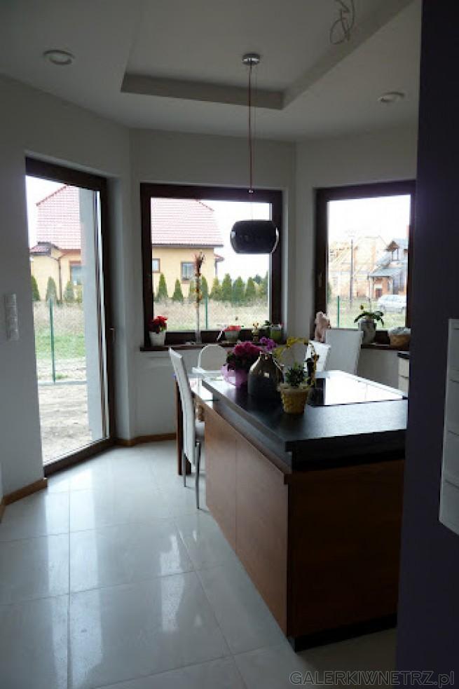Biała kuchnia, oświetlona i powiększona optycznie dzięki dużym oknom i drwiom ...