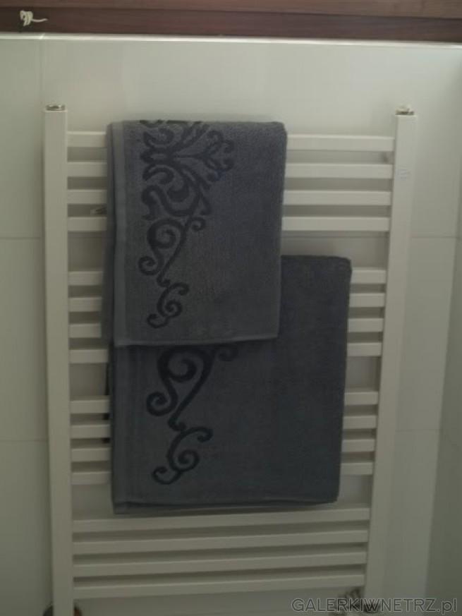Kaloryfer, będący jednocześnie wieszakiem na ręczniki, zamontowany pod okienkiem