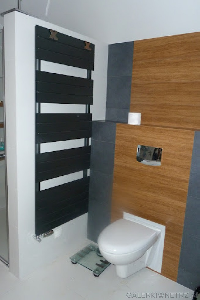 WC zamontowane na ciemnobrązowej ścianie. Grzejnik w kolorze grafitowym