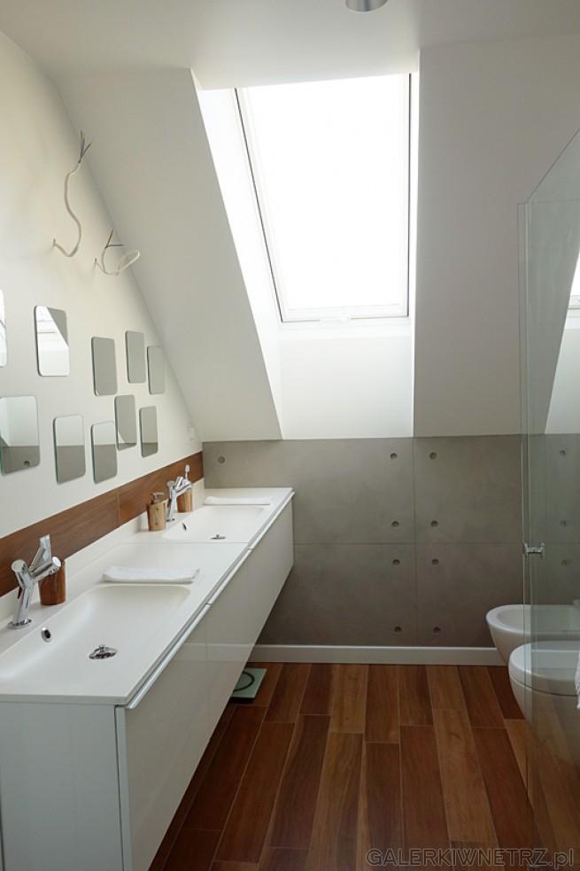 Przykład aranżacji łazienki ze skosem. Dominuje tu biel oraz brąz. Na podłodze ...
