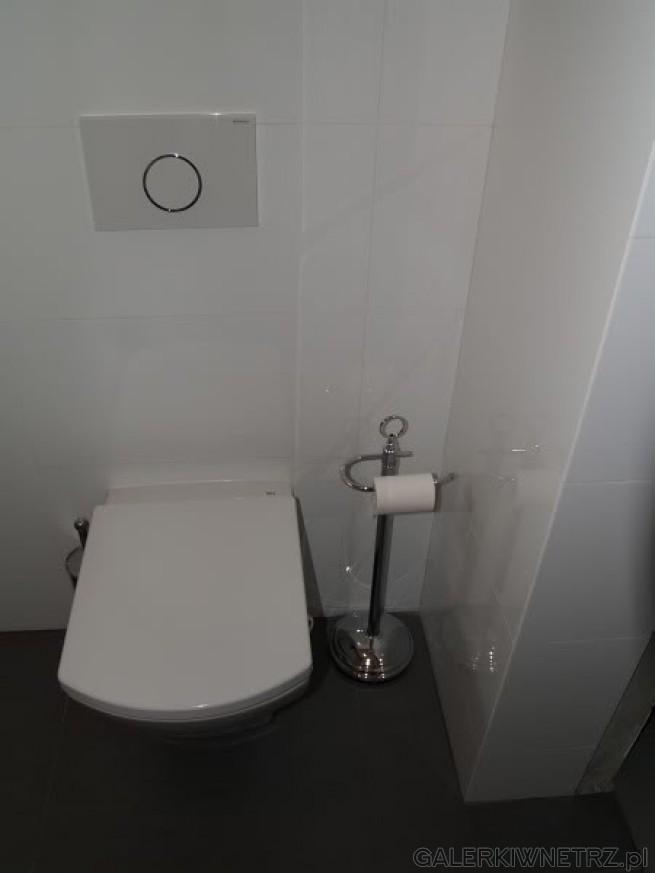 WC na ścianie, pokrytej dużymi białymi Płytkami