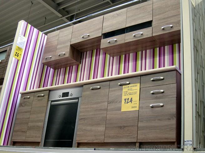 Połączanie kolorowej ściany w paski z tradycyjnymi meblami drewnianymi do kuchni. ...
