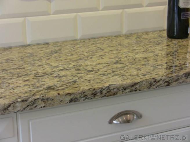 W tej aranżacji kuchennej wykorzystano jasny blat granitowy, a pod nim białe szuflady ...