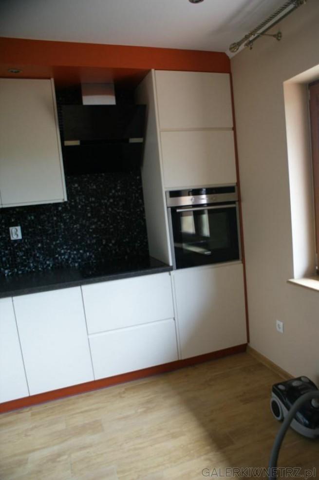 Jasna kuchnia z niewielkim oknem, białe szafki, oświetlenie sufitowe